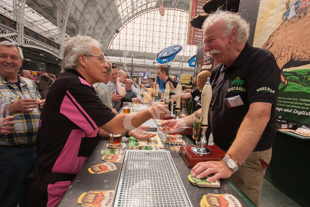 Olympia, London, August 12th 2014. Visitors to the CAMRA Great British Beer Festival sample Hog's Back Brewery's ales.