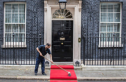 © Licensed to London News Pictures. 15/09/2015. London, UK. A man sweeps red carpet outside Number 10 Downing Street before Prime Minister David Cameron met with Polish President Andrzej Duda.  Photo credit : James Gourley/LNP