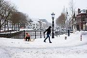 In Utrecht trekt een vrouw een kind op een slee voort in de sneeuw.<br /> <br /> In Utrecht, a woman pulls a child on a sledge in the snow.