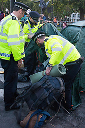 London, UK. 9 October, 2019. Police officers using Section 14 of the Public Order Act 1986 remove tents pitched by activists from Extinction Rebellion around Parliament Square on the third day of International Rebellion protests to demand a government declaration of a climate and ecological emergency, a commitment to halting biodiversity loss and net zero carbon emissions by 2025 and for the government to create and be led by the decisions of a Citizens' Assembly on climate and ecological justice.