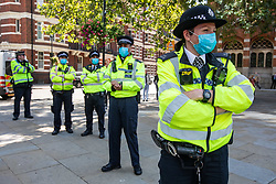 © Licensed to London News Pictures. 01/09/2020. London, UK. Police in medical mask follow members of Extinction Rebellion as they make their way to Parliament Square. Extinction Rebellion (XR) environmental campaign group are to gather in Parliament Square in central London as they start their sit-in today to blockade Parliament. XR plan to peacefully disrupt the UK Parliament with actions planned over two weeks, until MP's back the Climate Ecological Emergency Bill and prepare for crisis with a National Citizens's Assembly. Photo credit: Alex Lentati/LNP