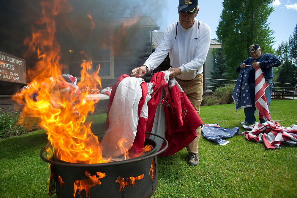 PRICE CHAMBERS / NEWS&GUIDE<br /> Cliff Poindexter places the stripes of an American Flag into the fire as Don Perkins separates the stars of Old Glory at American Legion Post 43 on Friday during a Flag Day ceremony to properly dispose of worn flags.