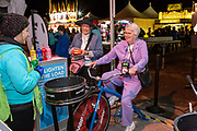 Sue Patton rides a spin art bike as Sue Gruesser looks on at the AARP Block Party at the Albuquerque International Balloon Fiesta in Albuquerque New Mexico USA on Oct. 8th, 2018.
