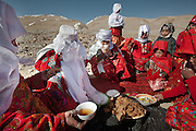 """Ikhbal (hiding under the white veil) and sister Irasia arriving at Tash Seri camp (Mustafa Qol's camp) and being welcomed with """"Borsot"""" (fried dough), yoghurt and tea by the local women of Tash Seri..With Ikhbal, the recently married woman  moving for the first time to her husband's camp. She just exchanged the red veil of the unmarried girl for the white veil signifying that she is now a married woman...Trekking through the high altitude plateau of the Little Pamir mountains, where the Afghan Kyrgyz community live all year, on the borders of China, Tajikistan and Pakistan."""