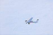 A Homer Air cessna 206 flies over the ice fields of the Kenai Mountain Rage during a flightsee from Homer, Alaska.