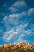 A vertical image of the clouds above the summit of Diamond Head Crater in Honolulu, Hawaii