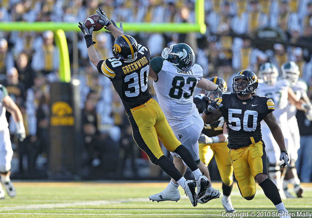 October 30 2010: Iowa Hawkeyes cornerback Brett Greenwood (30) pulls in an interception on a pass intended for Michigan State Spartans tight end Charlie Gantt (83) during the third quarter of the NCAA football game between the Michigan State Spartans and the Iowa Hawkeyes at Kinnick Stadium in Iowa City, Iowa on Saturday October 30, 2010. Iowa defeated Michigan State 37-6.