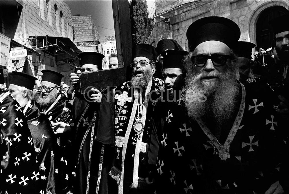 Greek Orthodox priests walk up the Via Dolorosa marking the Stations of the Cross during Holy Week Jerusalem Israel