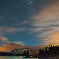 Stars and lingering alpenglow hover over Mount Rundle and Two Jack Lake.