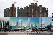 A man rides a motorbike past new apartment building developments seen standing behind propaganda for the Chinese Communist Party in Kunshan, Jiangsu Province, China on 25 October, 2011. As China's central government shows no intention to loosen its policy restrictions on the housing market despite 4 consecutive  months of price drops,  local governments must find a way to repay the 10.7 trillion yuan ($1.7 trillion) in debt as their land sale revenue dropped 13 percent from the previous year and with no end in sight.