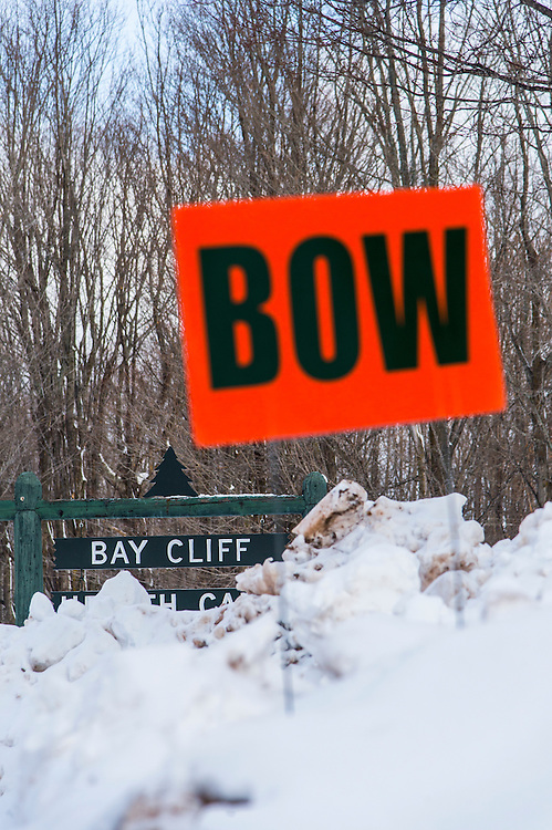 Signs for the Michigan DNR Becoming an Outdoors Woman program in a snowbank at Bay Cliff Health Camp in Big Bay, Michigan.
