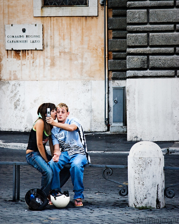 A young couple sitting on a rail in a piazza and posing for a photo taken with his mobile phone. (Rome, Italy)