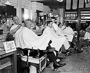 Y-500703B.  Heathman Hotel barbershop open on July 4th weekend. In the background through the window is the Broadway Theatre. July 3, 1950