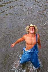 Shirtless young man wearing overalls and straw hat standing in a stream enjoying a rain shower