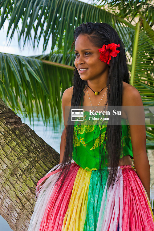 Girl in traditional dress with palm tree, Palau, Micronesia