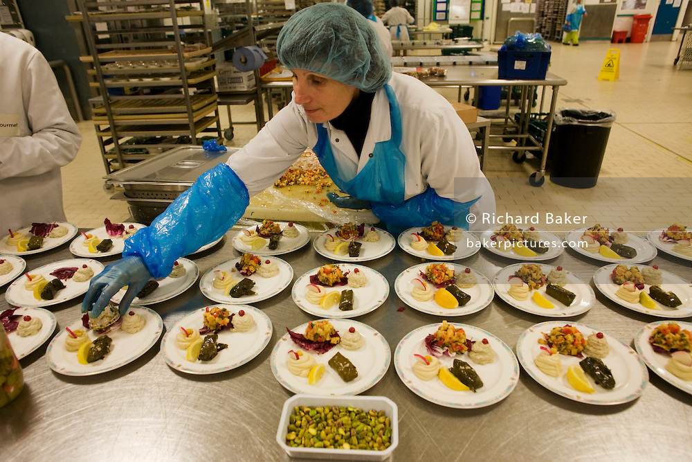 """A lady employee of the world's largest independent provider of airline catering and provisioning services, Gate Gourmet, reaches out to add the last items in the company's factory on the southern perimeter road at Heathrow Airport, West London. Gate Gourmet serve more than 200 million meals on 2 million airline flights a year to their 250-plus airline customers at more than 100 airport locations around the globe. Apart from creating the bespoke meals for an airline's culture and ethnic demands, that pack the pre-flight carts, deliver and load into the aircraft galleys and afterwards, they dispose of the waste and strip, wash and sterilize the equipment. From writer Alain de Botton's book project """"A Week at the Airport: A Heathrow Diary"""" (2009). ."""