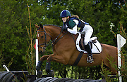 Young woman rides a dark bay horse in an eventing competition, United Kingdom