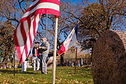 11 NOVEMBER 2020 - DES MOINES, IOWA: ROBERT NIFFENEGGER, right, reads the names of veterans buried in Woodland Cemetery, wile ALAN WENGER, left, and MIKE ROWLEY, members of Sons of the Revolution, listen during the Veterans' Day service in Woodland Cemetery in Des Moines. Volunteers read the names of the approximately 1,000 veterans buried in the cemetery. The observance at Woodland Cemetery was one of the few live Veterans Day ceremonies in the Des Moines area this year. Most were held online only because of the Coronavirus pandemic.  PHOTO BY JACK KURTZ