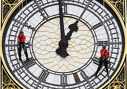 Height safety specialists Taskmasters (in red) abseil down St. Stephens Tower, which houses Big Ben in Westminster, central London, to aid heritage glazier Tony McGilbert (in blue), to evaluate and conduct repairs while the clock's hands are in motion.