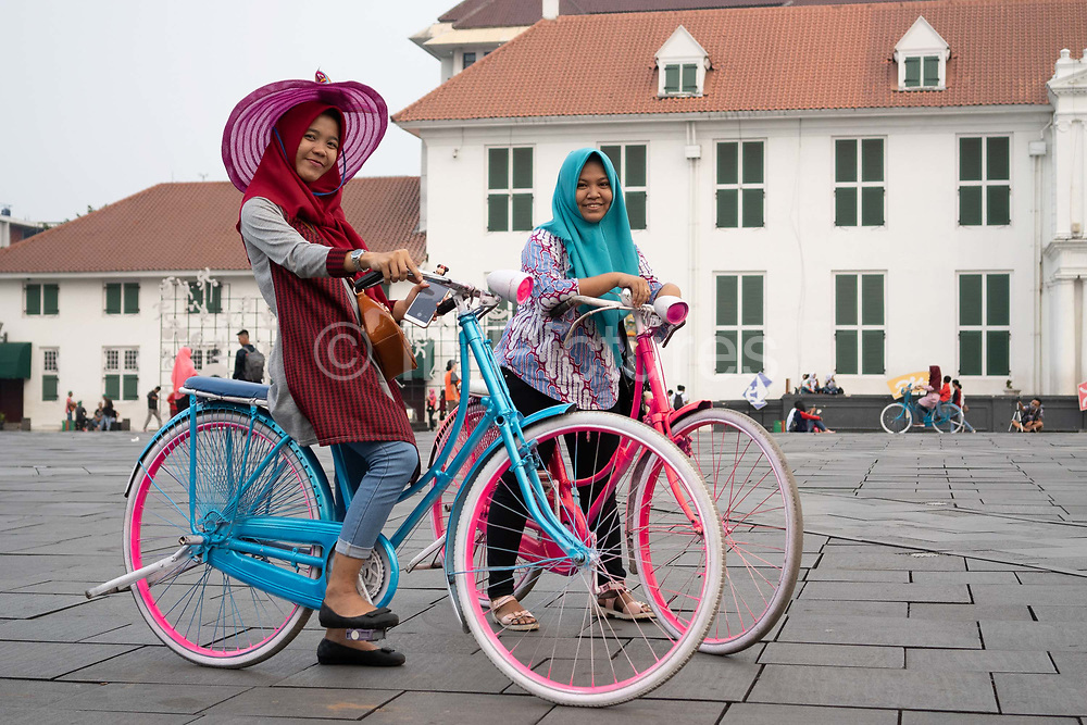 Indonesian tourists ride around on colourful bikes in Fatahillah Square on 8th June 2018, Jakarta, Java, Indonesia. The square is a popular destination for national and international tourists alike.