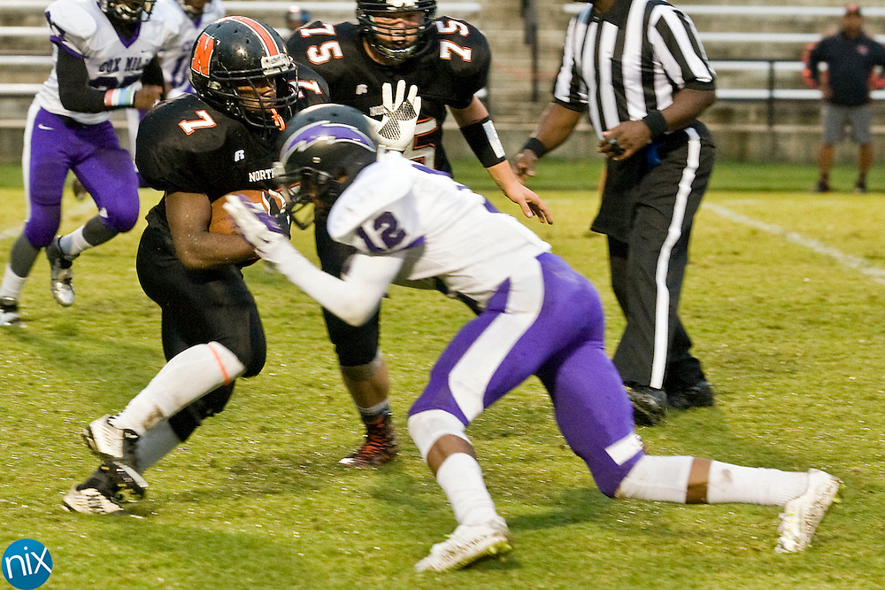 Trojans running back Omar Kiser (7, left) is hit by Chargers defensive back Justin Ford (12, right) during the Cox Mill Chargers at Northwest Cabarrus Trojans high school football game on Friday night.