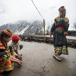 Kalash children playing with marbles on the roof terraces of their village in Bumburet,Chitral District,Pakistan.