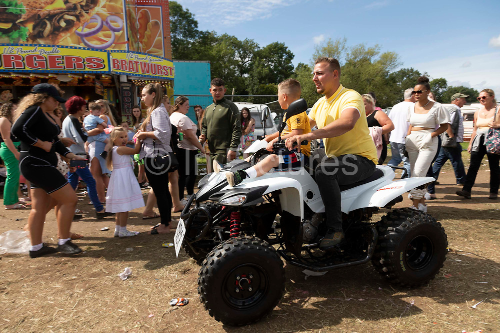 A man rides a quad bike with a child on the front on the fair ground at Appleby Horse Fair, the biggest gathering of Gypsies and travellers in Europe, on 14th August, 2021 in Appleby, United Kingdom. Appleby Horse Fair attracts thousands from Gypsy, Romany, and traveller communities annually, making it the biggest gathering of its kind in Europe. Generally held for a week every June, the fair was postponed in 2020 and pushed forward to August in 2021 due to Coronavirus.