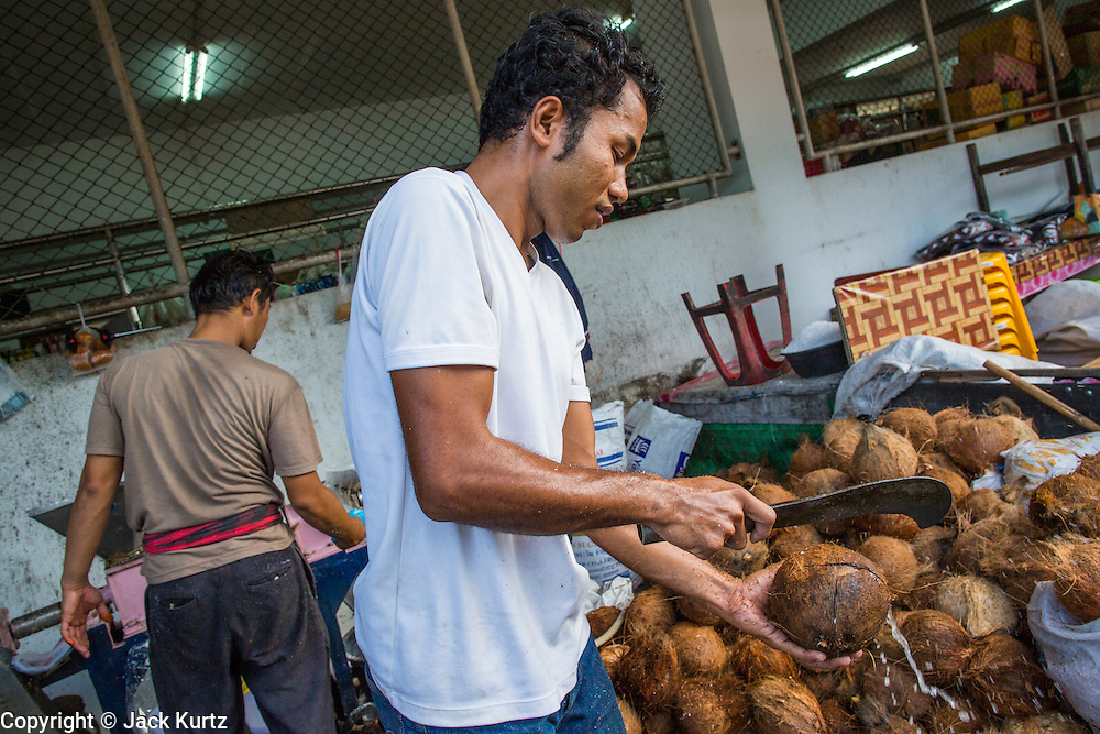 25 OCTOBER 2012 - PATTANI, PATTANI, THAILAND: A man cuts open coconuts in the market in Pattani, Thailand.     PHOTO BY JACK KURTZ