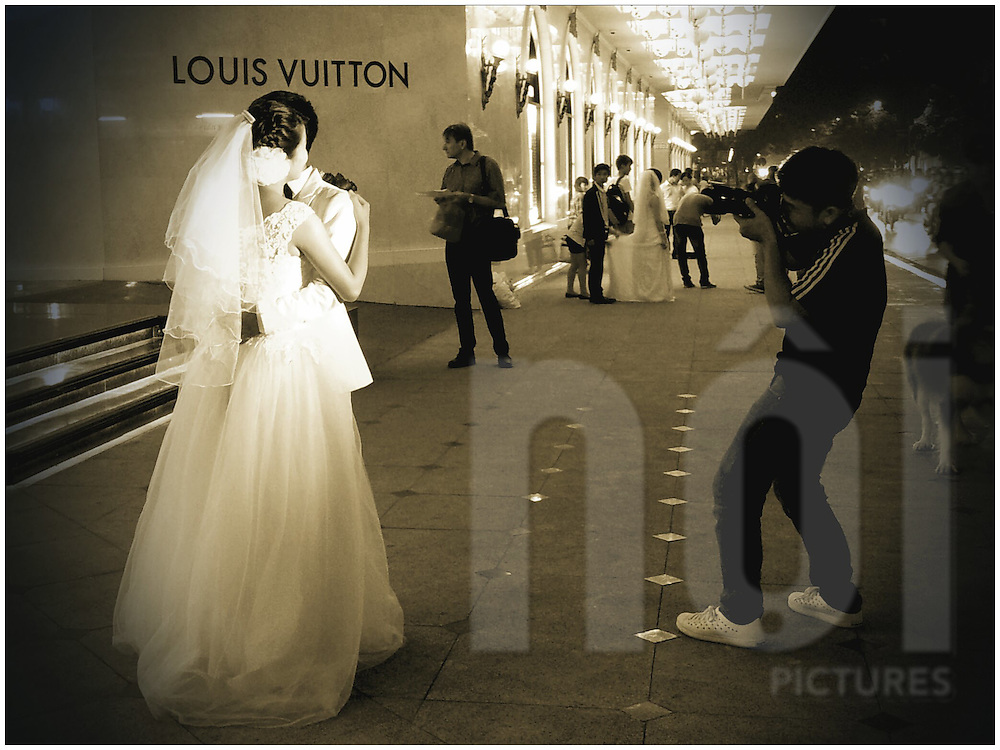 Brides and grooms pose for wedding photos outside of Trang Tien Plaza in Hanoi, Vietnam, Southeast Asia