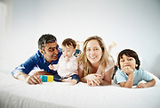Parents with a toddler and young son play on bed.