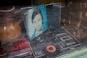 Old discs of faded music stars and a record player in the window of a corner shop in Letna, Holesovice district, Prague 7, on 18th March, 2018, in Prague, the Czech Republic.
