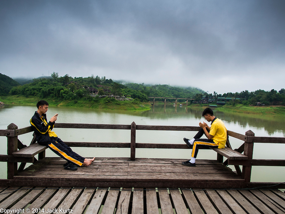 16 SEPTEMBER 2014 - SANGKHLA BURI, KANCHANABURI, THAILAND:  Boys read the school books on a repaired span of the Mon Bridge in Sangkhla Buri. The 2800 foot long (850 meters) Saphan Mon (Mon Bridge) spans the Song Kalia River. It is reportedly second longest wooden bridge in the world. The bridge was severely damaged during heavy rainfall in July 2013 when its 230 foot middle section  (70 meters) collapsed during flooding. Officially known as Uttamanusorn Bridge, the bridge has been used by people in Sangkhla Buri (also known as Sangkhlaburi) for 20 years. The bridge was was conceived by Luang Pho Uttama, the late abbot of of Wat Wang Wiwekaram, and was built by hand by Mon refugees from Myanmar (then Burma). The wooden bridge is one of the leading tourist attractions in Kanchanaburi province. The loss of the bridge has hurt the economy of the Mon community opposite Sangkhla Buri. The repair has taken far longer than expected. Thai Prime Minister General Prayuth Chan-ocha ordered an engineer unit of the Royal Thai Army to help the local Mon population repair the bridge. Local people said they hope the bridge is repaired by the end November, which is when the tourist season starts.   PHOTO BY JACK KURTZ