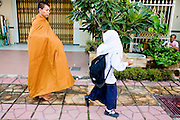 """Sept. 25, 2009 -- PATTANI, THAILAND: A Thai Muslim girl walks past a Thai Buddhist monk on his morning rounds in Pattani, Thailand. Thailand's three southern most provinces; Yala, Pattani and Narathiwat are often called """"restive"""" and a decades long Muslim insurgency has gained traction recently. Nearly 4,000 people have been killed since 2004. The three southern provinces are under emergency control and there are more than 60,000 Thai military, police and paramilitary militia forces trying to keep the peace battling insurgents who favor car bombs and assassination.  Photo by Jack Kurtz / ZUMA Press"""