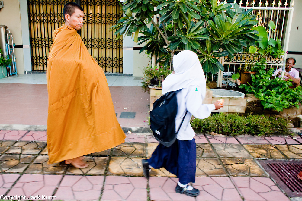 "Sept. 25, 2009 -- PATTANI, THAILAND: A Thai Muslim girl walks past a Thai Buddhist monk on his morning rounds in Pattani, Thailand. Thailand's three southern most provinces; Yala, Pattani and Narathiwat are often called ""restive"" and a decades long Muslim insurgency has gained traction recently. Nearly 4,000 people have been killed since 2004. The three southern provinces are under emergency control and there are more than 60,000 Thai military, police and paramilitary militia forces trying to keep the peace battling insurgents who favor car bombs and assassination.  Photo by Jack Kurtz / ZUMA Press"