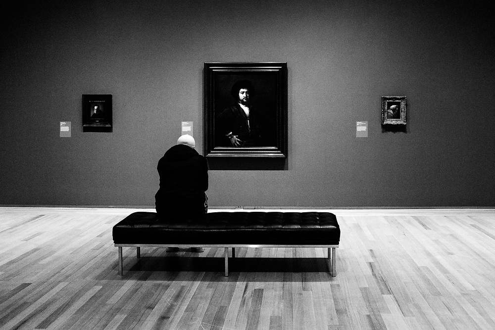 A young man named Benjamin sits and looks bored in front of a Rembrandt painting in Kingston, Ontario art gallery called the Agnes Etherington Art Centre.
