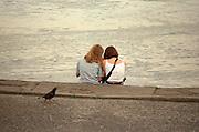 Friends age 21 talking on the banks of the Vistula River.  Torun Poland