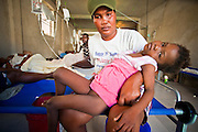 18 NOVEMBER 2010 - PORT-AU-PRINCE, HAITI: Jeangina Givenchie holds her daughter, Nikola, while the girl is treated for cholera in a Medicins Sans Frontieres (MSF - Doctors Without Borders) cholera stabilization center in Cite Soliel in Port-au-Prince. Cite Soleil, a sprawling slum area in PAP is ground zero for the cholera epidemic in the Haitian capital. An outbreak of cholera in northern Haiti about a month ago has spread across the nation. Tens of thousands of people have been hospitalized and treated for cholera and more than 1,100 have died. Cholera is a water borne illness that causes severe diarrhea and death by dehydration in a matter of hours.      PHOTO BY JACK KURTZ  choleraepidemic