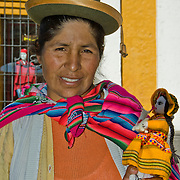 """Woman offering her handmade dolls in the """"White City"""" of Arequipa, Peru."""