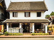 "12 MARCH 2016 - LUANG PRABANG, LAOS: A colonial style shophouse turned into tourists' boutiques and souvenir shops in Luang Prabang. Luang Prabang was named a UNESCO World Heritage Site in 1995. The move saved the city's colonial architecture but the explosion of mass tourism has taken a toll on the city's soul. According to one recent study, a small plot of land that sold for $8,000 three years ago now goes for $120,000. Many longtime residents are selling their homes and moving to small developments around the city. The old homes are then converted to guesthouses, restaurants and spas. The city is famous for the morning ""tak bat,"" or monks' morning alms rounds. Every morning hundreds of Buddhist monks come out before dawn and walk in a silent procession through the city accepting alms from residents. Now, most of the people presenting alms to the monks are tourists, since so many Lao people have moved outside of the city center. About 50,000 people are thought to live in the Luang Prabang area, the city received more than 530,000 tourists in 2014.       PHOTO BY JACK KURTZ"