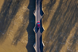 © Licensed to London News Pictures. 23/12/2019. Yalding, UK. A car crosses a bridge over the River Medway as brown coloured flood water flows beneath near Yalding in Kent. River levels are slowly beginning to drop after days of heavy rain in the south. Photo credit: Peter Macdiarmid/LNP