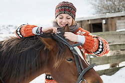 Young woman adjusting bridle her horse for riding, Bavaria, Germany