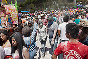 Carnival revellers covered in talcum powder, crowd shot. The annual Carnival in Zoque Coiteco, a district of Chiapas in Southern Mexico happens in the five days preceeding Ash Wednesday along with Carnival throughout the Americas. Participants dress in colourful costumes with masks depicting famous political and entertainment figures, and throw talcum powder at each other.