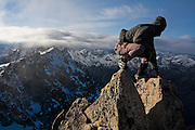 Climber Obadiah Reid stands on the summit block of Dragontail Peak, Alpine Lakes Wilderness, Washington. Mount Stuart is barely visible in the background.