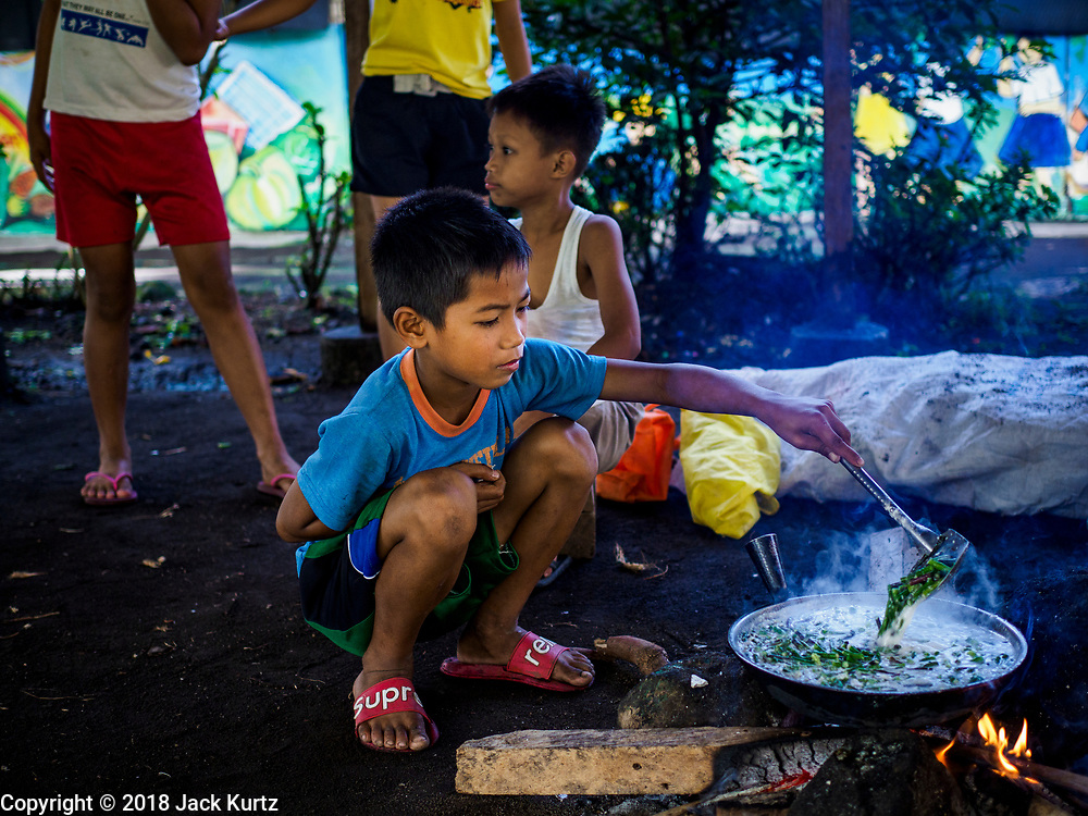 20 JANUARY 2018 - CAMALIG, ALBAY, PHILIPPINES: CARLO SACAYAN, 8, cooks green beans with coconut milk for his mother at the Barangay Cabangan evacuee shelter in a school in Camalig. The family will eat some of the food and sell some of it. There are about 650 people living at the shelter. They won't be allowed to move back to their homes until officials determine that Mayon volcano is safe and not likely to erupt. More than 30,000 people have been evacuated from communities on the near the Mayon volcano in Albay province in the Philippines. Most of the evacuees are staying at school in communities outside of the evacuation zone.  PHOTO BY JACK KURTZ