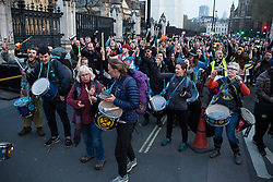 London, UK. 17th April 2019. Drummers from climate change action movement Extinction Rebellion march around Parliament Square during a police operation to clear protesters taking part in the International Rebellion in order to reopen the square to traffic.