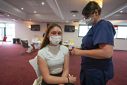 """© Licensed to London News Pictures. 10/07/2021. Sheffield, UK. Anna Martin,18, receives the first dose of the Pfizer/BioNTech vaccine at a pop-up vaccination clinic at Bramall Lane, home to Sheffield United football club in Sheffield, as part of the """"Grab a jab"""" campaign. Photo credit: Ioannis Alexopoulos/LNP"""