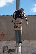 Bolivia June 2013. El Alto. Dummies strung up on the street to warn thieves that the community will not tolerate them. The sign says neighbours beware.