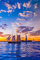 Sailing ship in New York harbor at sunset passes in front of the Statue of Liberty, New York, New York USA.