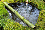 fresh water fountain made from stone moss and bamboo at the Kifune shrine in Kyoto Japan