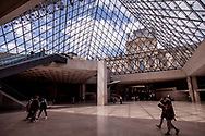 People walking with masks under Louvre's pyramid.